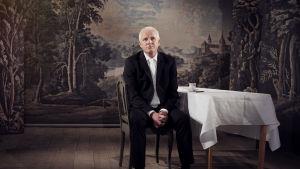 Karaktären Björn sitter ensam vid ett bord med vit duk i filmen Småstad.