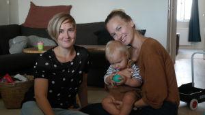 Doulakordinator Liisa Jungar sitter på golvet hos Inka-Maria Pulkkinen och hennes son Gabriel Nyman