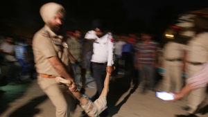 Poliser i Amritsar bär en kropp.