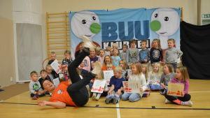Buu-klubbs-ledaren Jonathan Granbacka hoppar in i bild tillsammans med ett gäng dagisbarn från Vörå.