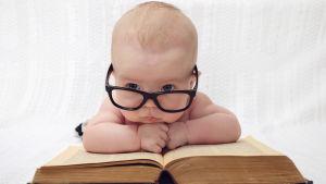Bebis med glasögon som ligger på en bok och funderar.