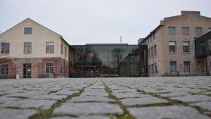 Arkens mittgård, fyrkantig stenläggning på marken. Gråmulet väder.