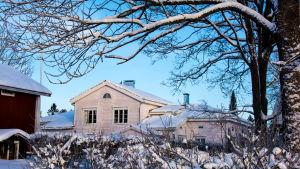 Gammal gårdsbyggnad i vinterskrud.
