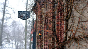 En röd tegelbyggnad med lyktor vi dörren. En gammaldags skylt där det står Slottskrogen. Träd i bakgrunden.