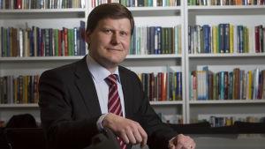 Forskningsledare Ilkka Haavisto sitter vid ett bord med böcker i bakgrunden.