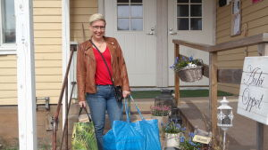 Terhi Pilke står på trappan med kassar i handen utanför sin butik Amalias hem i Korpo