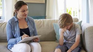 liten pojke sitter på soffan tillsammans med en socialarbetare. Pojken är ledsen.