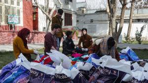 Frivilliga afghanska ungdomar sorterar kläder som ska doneras till bostadslösa i Afghanistan.