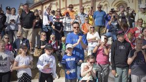 en publik applåderar och fotar med mobiltelefoner i sommarväder