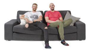 Juha ja Markus hymyilevät sohvalla.