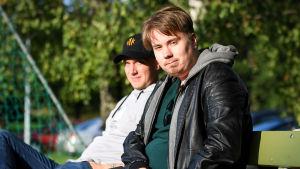 Toni Wistbacka (bakgrunden) och Dan Sandberg sitter på en bänk.