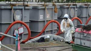 En person med en vit skyddsdräkt, andningsskydd och en vit hjälm på huvudet går förbi en lång rad containrar med radioaktivt vatten.