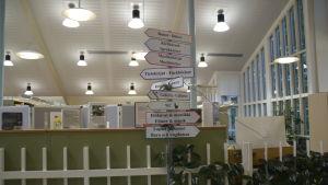 Hemgjorda textade skyltar i ett bibliotek som pekar åt vilket håll bland annat barnböcker, fackböcker och filmer finns. Många skyltar på en stolpe, mitt i ett bibliotek.