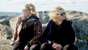 Inger Nilsson och maria Sid sitter på klippa med havet i bakgrunden medan deras hår fladdrar i vinden.