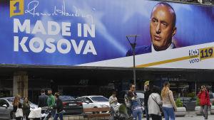 Människor går förbi en valaffisch i Pristina.