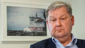Jan Hanses vd för Viking Line tittar in i kameran. Bilden tagen lite nedifrån och i bakgrunden syns en inramad bild av ett vikinglinefarttyg.