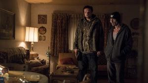 Två män med ovårdade kläder i ett dunkelt vardagsrum ser frågande mot någon bakom ett bord.