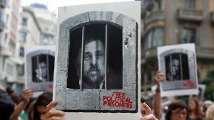 En demonstrant håller upp en skylt som föreställer den tidigare vice regionpresidenten i Katalonien Oriol Junqueras som dömdes till 13 års fängelse.