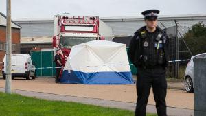 Till höger en polis. I bakgrunden ett blåvitt tält och bakom det en röd lastbil.