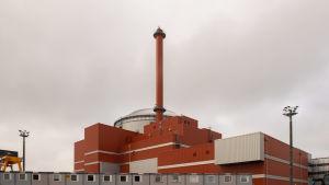 En röd skorsten står upp från de röda och vita byggnaderna på kärnkraftverket Olkiluoto 3.
