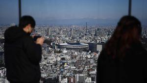 Människor ser ut över Tokyos nya olympiastadion från ett utsiktstorn den 30.11.2019.
