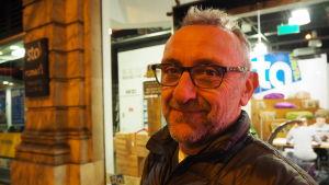 Colin Hatfield ler mot kameran på en gata i London.