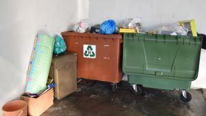 Två avfallsbehållare fyllda med skräp. Framför behållarna står en gammal kappsäck, en madrass och en låda med diverse skräp.