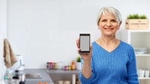 Äldre leende kvinna håller upp mobiltelefon mot kameran