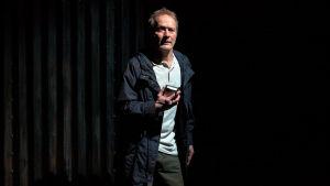 En medelålders man står på en mörk scen med en bandspelare i handen.