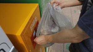 Plastpåse som en kinesisk perosn håller i