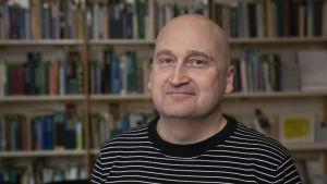 En man står framför en bokhylla.