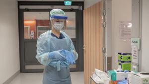 Lääkäri pukee suojavarustusta