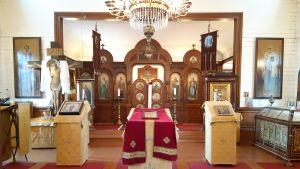 Rött och guld dominerar interiören i Hangö ortodoxa kyrka. Kyrkoväggarna är vita.