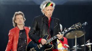 På bilden syns rockbandet Rolling Stones uppträda under en konsert i Berlin år 2018. I förgrunden syns gitarristen Keith Richards iklädd svarta kläder och en färggrann bandana.