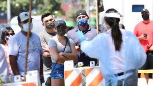 En frivilligarbetare gav anvisningar till människor som köade till en testplats i Los Angeles i fredags.