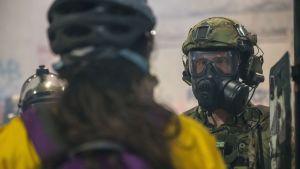 En demonstrant och en federal polis stirrar varandra i ögonen under en demonstration i Portland den 21 juli.