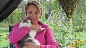 En kvinna sitter ute, under ett partytält/paviljong och håller en katt i famnen. Sommar, mycket blommor och grönt.