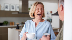 Leende kvinna med kaffekopp och man med ryggen mot kameran
