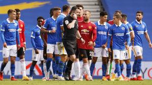 Brighton- och Man United-spelare samlade runt domaren Chris Kavanagh som pratar i sitt headset.