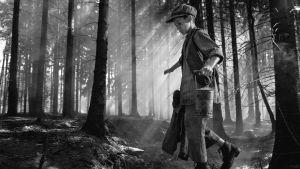 Den lilla pojken Joska balanserar på en stock i en skog med vattenhink i ena handen.