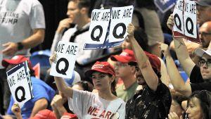 """Vaalitilaisuuden yleisössä joukko ihmisiä pitää esillä kylttejä, joissa lukee """"We are Q"""" eli """"Me olemme Q""""."""