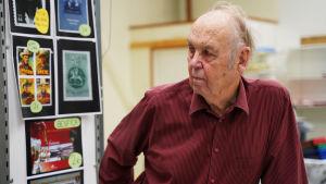 Olli Peltonen står bredvid en frimärkssamling.