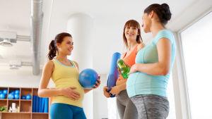 Tre gravidakvinnor i träningskläder ler mot varandra