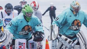 Flera personer iklädda ishockeyutrustning åker skridsko på istäckt sjö i grått och blött väder.