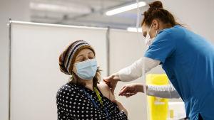 Kvinna iklädd i munskydd får en spruta i armen av en sköterska.