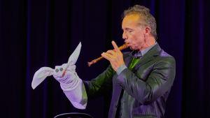 Vatsastapuhuja Frank Rossilla kangasnukke kädessä ja soittaa nokkahuilua
