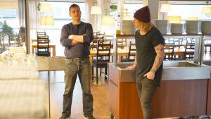 Två män står inne i en tom restaurang, de står på behörigt avstånd från varandra.