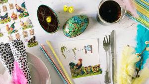Ett bord fullt med påskrelaterade prylar: ett kort med en tupp, två påskägg, ett glas med mjöd och några påskkvistar.