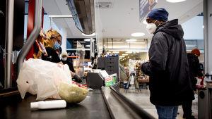 Henkilö ostoksilla ruokakaupassa.