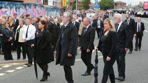 Svartklädda personer i ett begravningståg.